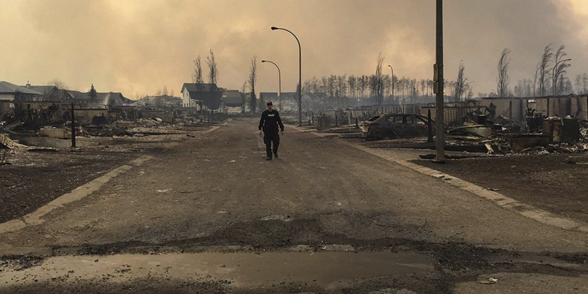 A Mounty examines fire damage in Fort McMurray (photo: RCMP)