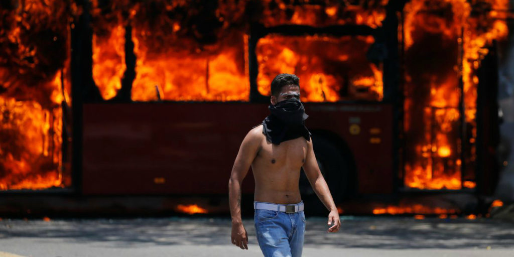 AP Photo of a coup supporter in front of a burning bus(photo: Fernando Llano)